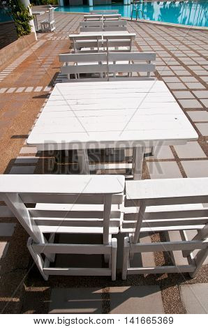 White wooden chair in swimming pool, empty