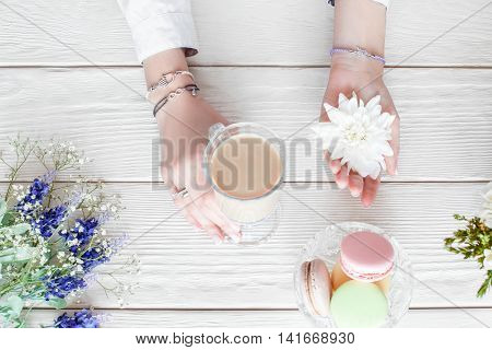 Romantic woman breakfast, flat lay. Beautiful female hands holding cup of coffee latte and white flower, dish with macaroon and flowers on white wooden background, top view