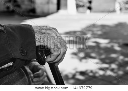 closeup of the hand of an old caucasian man with a walking stick, in black and white