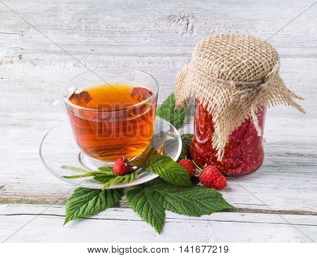 Homemade raspberry jam and transparent cup of tea with raspberry leaves and berry on wooden background