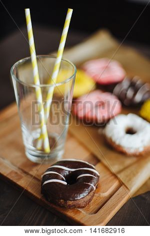 Chocolate donut with glass and straws close up.