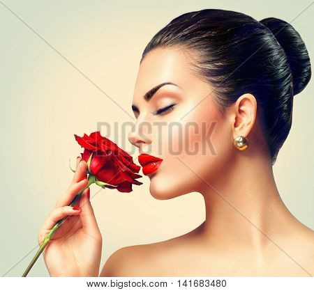 Beauty Woman with red rose. Fashion Brunette Model Girl face Portrait with Red Rose in her hand. Red Lips and Nails. Beautiful Luxury Makeup and Manicure. Vogue Style
