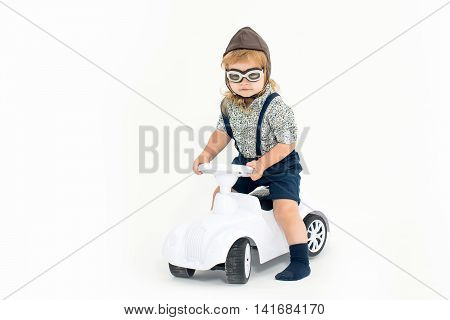 small boy kid driver or pilot sitting on plastic toy cat in stylish shirt helmet or hat and glasses isolated on white background