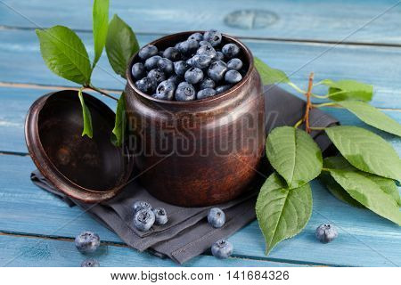 Freshly picked blueberries in metal bowl. Juicy and fresh blueberries with leaves on blue wooden table. Blueberry on wooden background. Blueberry antioxidant. Concept for healthy eating and nutrition.
