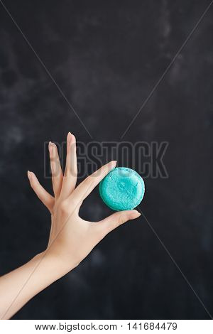 Macaroons almond cake in a woman's hand