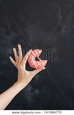 Pink strip donut in a woman's hand