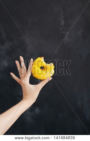 Yellow strip donut in a woman's hand