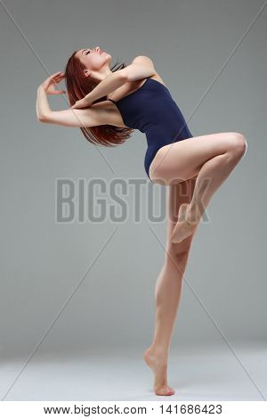 Beautiful ballet-dancer, modern style dancer posing on studio background. Contemporary