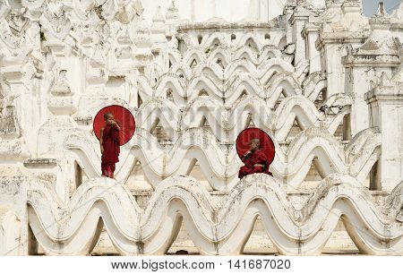BurmaThe Novice monk holding red umbrella on the pagoda