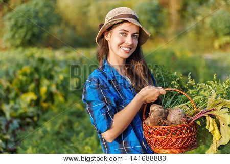 Gardener with freshly harvested vegetables in garden with sunlight. Portrait of happy woman with a basket of vegetables. Harvest.