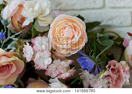 Beautiful intertwined flowers, peonies decorating the interior. White brick wall