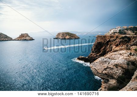 The yacht sails near the rocks of Santa Ponsa in the mediterranean sea before the storm Mallorca Island
