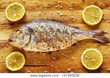 Roasted Gilt Head Bream Fish On A Wooden Table.