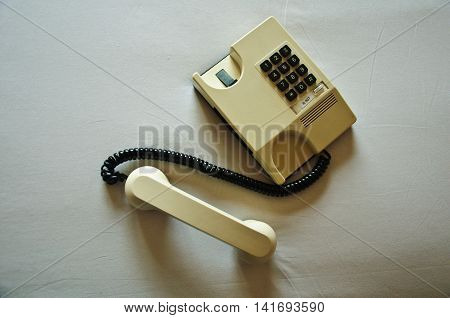 Office telephone set off-hook on table, old telephone