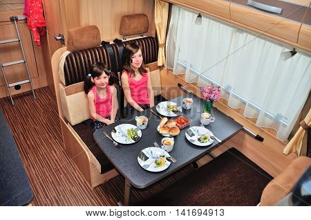 Family vacation, RV holiday trip, happy smiling kids travel on camper, children eating in motorhome interior poster