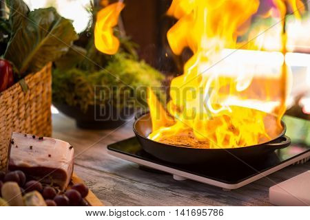 Fire in pan. Meat and spurts of flame. Steak is being fried. Danger and beauty.