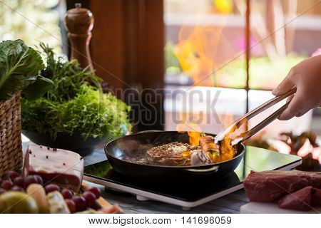 Tongs touching meat on pan. Food being fried. How to make flambe steak. Expensive dish in new restaurant.