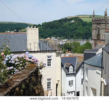 Picturesque view of historic houses, old church steeple, rustic wall and hilly landscape in the coastal British town of Dartmouth, Devon