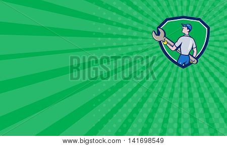 Business card showing illustration of a mechanic carrying giant spanner looking up to the side viewed from rear set inside shield crest on green sunburst background done in cartoon style.
