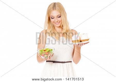 Half-length portrait of very beautiful woman holding cake and fresh vegetables. Young housewife choosing sweets or healthy eating - cake and salad. Laughing at camera. Isolated on white background.