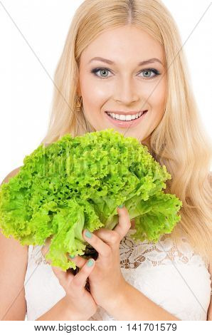 Half-length portrait of very beautiful woman holding fresh lettuce, green salad and looking at us. Studio shot isolated on white background. Healthy eating concept.