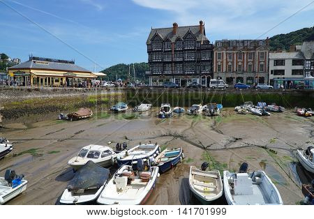 DARTMOUTH, UK - JULY 6: Crowds throng the South Embankment harbour promenade in the coastal riverside town of Dartmouth, Devon on July 6, 2016. Several small boats sit in a sheltered harbour area, at low tide.