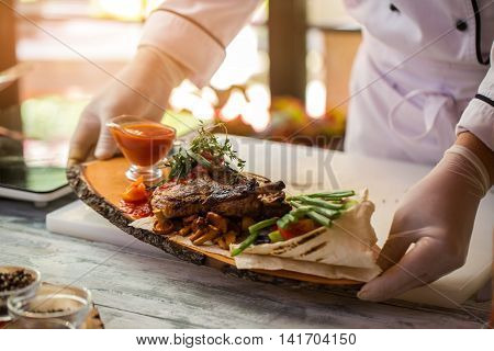 Cooked meat and pita bread. Hands hold board with food. Tasty dish with grilled pork. High calorie lunch in cafe.