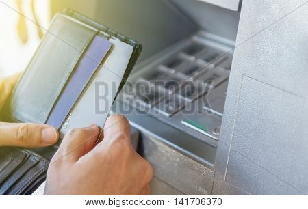 A woman is withdrawing money from an ATMCash withdrawal. Woman's hand inserting plastic card Visa into the ATMfinance conceptbusiness background and selective focus.