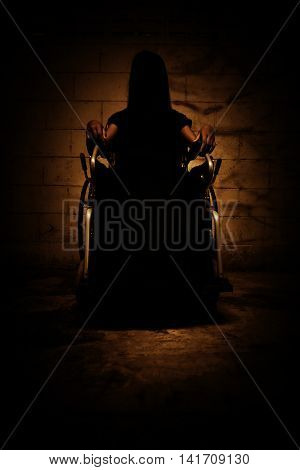 Ghost woman sitting on wheelchair in asylum,Scary background for book cover
