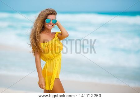 Beautiful young woman with long blond hair,standing on the white sand of a tropical beach near the blue ocean,dressed in a short transparent sleeveless yellow in color,wears blue mirror sun glasses posing against white waves of the ocean