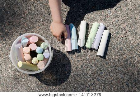 Picking a sidewalk chalk. Assortment of sidewalk chalks on asphalt.