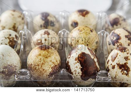 Little Quail Eggs In The Form Of Pre-packaged. Grey Stone Backgr
