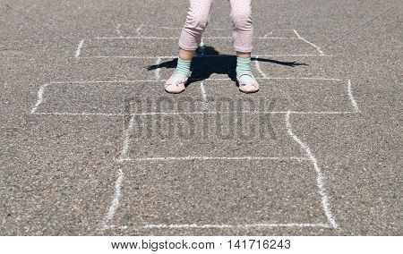 Girl hopping on a hopscotch game painted on pavement.