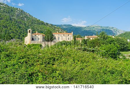 The medieval Podmaine Monastery surrounded by fortress wall located among the lush greenery in the former Maine settlement nowadays it's Budva Montenegro.