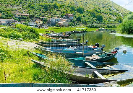 The port on Moraca River in Vranjina fishing village with many moored wooden punt boats Montenegro.