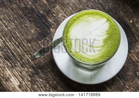 Matcha Latte Green Tea on Wooden Background table.