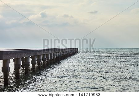 Perspective view of a wooden pier with sun rays over the sea