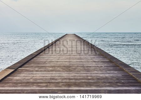 Perspective view of a wooden pier in a tropical sea