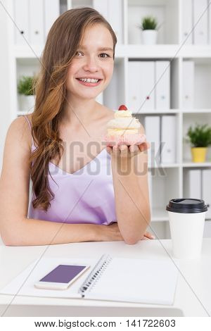 Young girl holding cupcake and smiling to camera. Her smart phone coffee and notebook lie on table. Concept of tasty food anticipation at office.