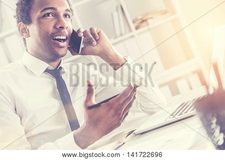Side view of attractive african american businessman using notepad and laptop computer on office desktop while having mobile phone conversation.Bookshelf with documents in the background.Toning filter