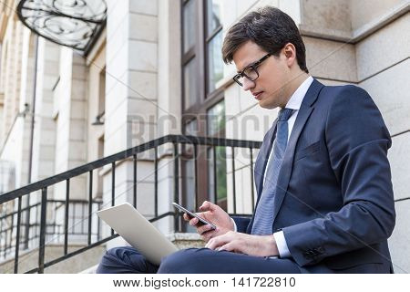 Side view of young businessman sitting outside on building stairs using laptop and smartphone. Teleworking young man