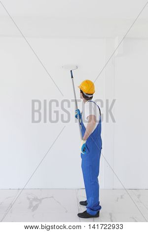 Young worker in hardhats painting the wall