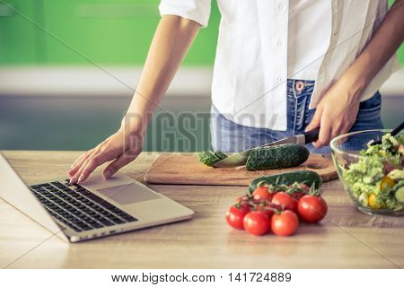 Cropped image of beautiful girl using a laptop and holding a knife while cutting cucumber for salad in her kitchen at home