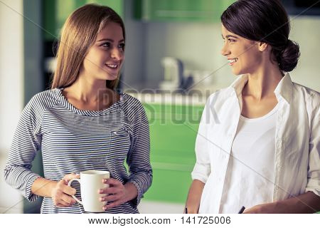 Two beautiful girls are talking looking at each other and smiling while standing in the kitchen at home. One girl is holding a cup