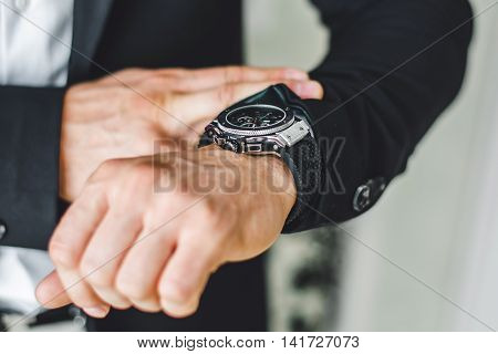 businessman looking at his watch on his hand watching the time