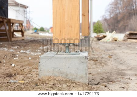 Wooden pillar on the construction site concrete with screw. Wooden Pillars are structures that can be placed on Foundations or Platforms.
