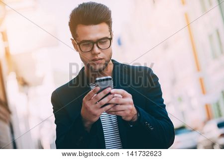 Quick message to friend. Handsome young man in smart casual wear holding smart phone and looking at it while walking along the street