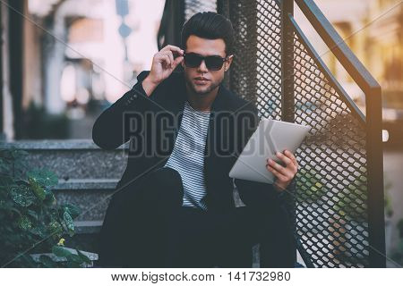 Confident handsome. Handsome young man in smart casual wear carrying digital tablet while sitting on stairs outdoors