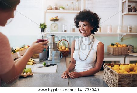 Portrait of smiling young african woman standing behind juice bar counter and talking with customer holding a glass of fresh juice.