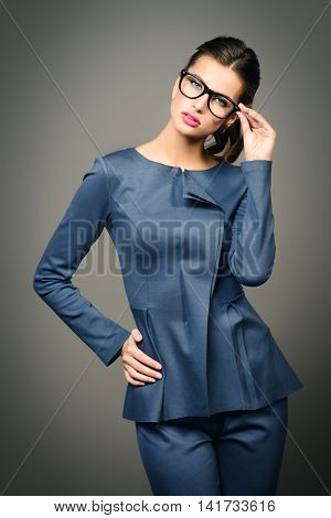 Optics style. Portrait of a beautiful young woman wearing elegant suit and glasses. Beauty, fashion. Cosmetics, make-up.